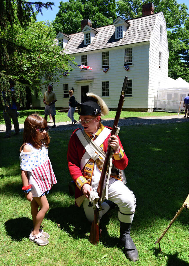 Revolutionary War re-enactor Chris Murphy, with the British Seventh Company of the Ninth Regiment of Foot, talks to Alessandra Tuccillo, 6, of Fairfield, during Family Fun Fest held on the Town Hall Green and the Fairfield Museum and History Center in Fairfield, Conn. on Saturday July 5, 2014. The festival featured a full slate of musical entertainment, artisan fair, and games and activities for children. Photo: Christian Abraham / Connecticut Post