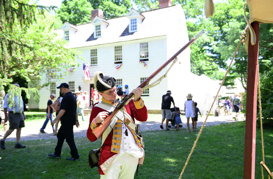 Revolutionary War re-enactor Chris Murphy, with the British Seventh Company of the Ninth Regiment of Foot, inspects his musket rifle during Family Fun Fest held on the Town Hall Green and the Fairfield Museum and History Center in Fairfield, Conn. on Saturday July 5, 2014. The festival featured a full slate of musical entertainment, artisan fair, and games and activities for children. Photo: Christian Abraham / Connecticut Post