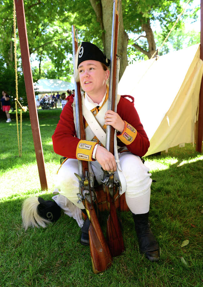 Sarah Murphy, a Revolutionary War re-enactor with the British Seventh Company of the Ninth Regiment of Foot, attends Family Fun Fest held on the Town Hall Green and the Fairfield Museum and History Center in Fairfield, Conn. on Saturday July 5, 2014. The festival featured a full slate of musical entertainment, artisan fair, and games and activities for children. Photo: Christian Abraham / Connecticut Post