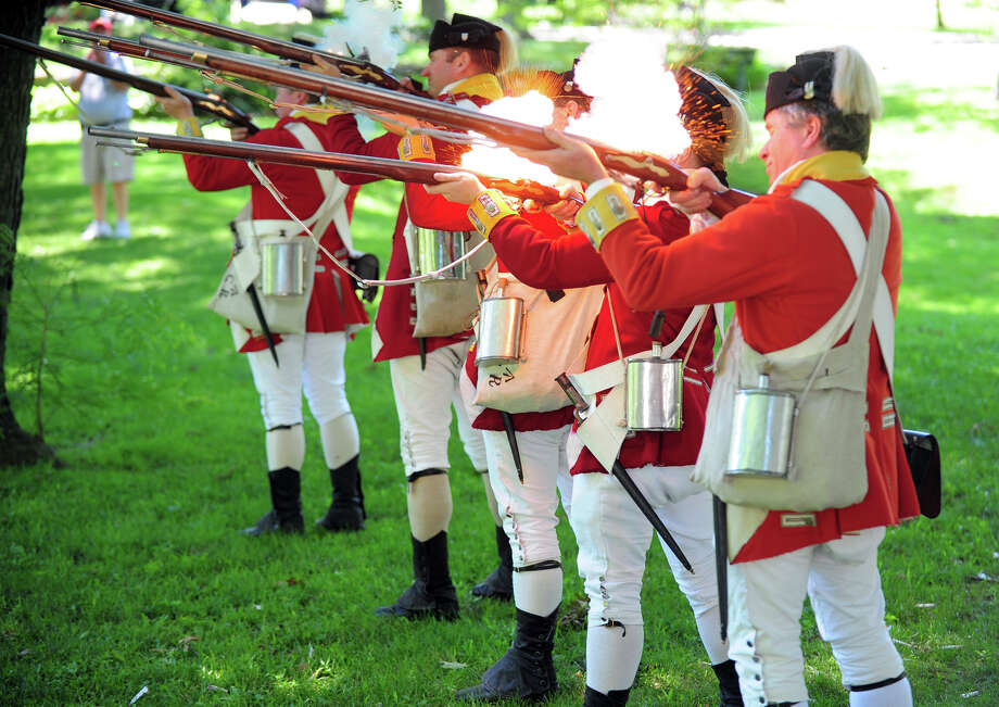 Revolutionary War re-enactors with the British Seventh Company of the Ninth Regiment of Foot, drill around the grounds, during Family Fun Fest held on the Town Hall Green and the Fairfield Museum and History Center in Fairfield, Conn. on Saturday July 5, 2014. The festival featured a full slate of musical entertainment, artisan fair, and games and activities for children. Photo: Christian Abraham / Connecticut Post