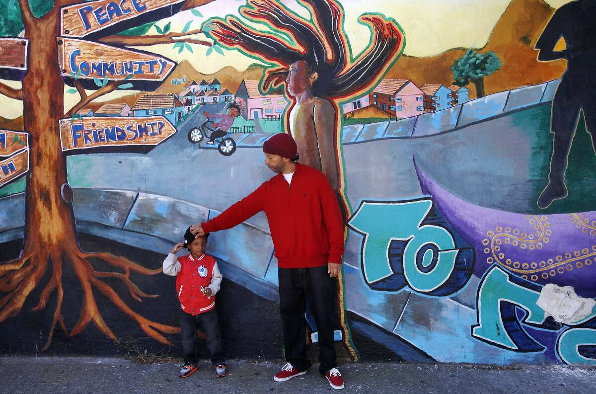 Sekou Carson adjusts the hat on his son Zakai Carson, 4, as they lean up against a community mural titled