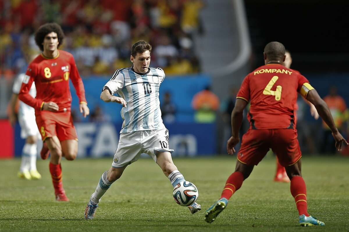 TOPSHOTS Argentina's forward and captain Lionel Messi (C) vies with Belgium's defender and captain Vincent Kompany during a quarter-final football match between Argentina and Belgium at the Mane Garrincha National Stadium in Brasilia during the 2014 FIFA World Cup on July 5, 2014. AFP PHOTO / ADRIAN DENNISADRIAN DENNIS/AFP/Getty Images