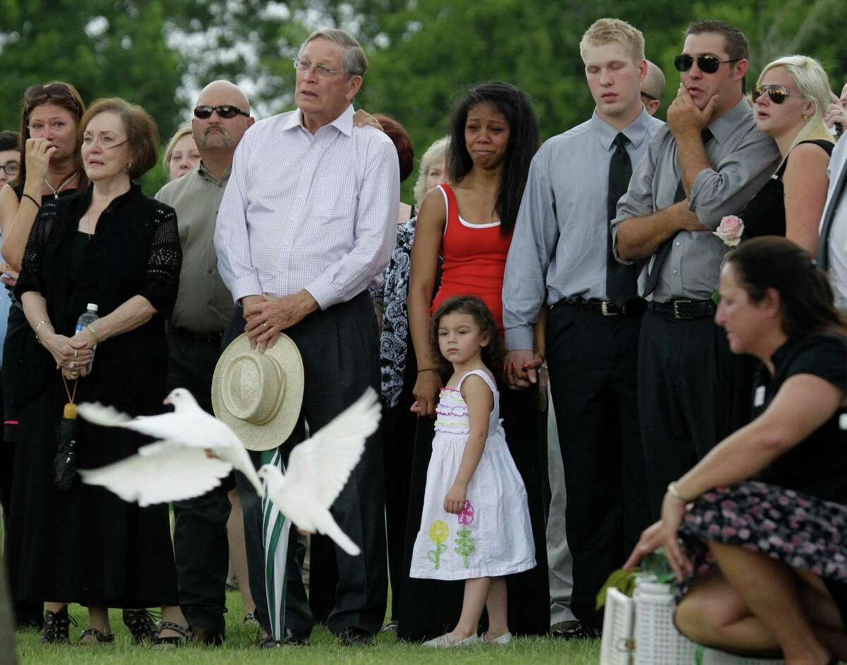 Mourners watch as white doves are released after the graveside services for 9-year-old Jason Frost, his mother, Kristina Cole Frost, and her sister, Leilani Rose Cole, at Rosewood Cemetery, 2602 South Houston Ave., Saturday, July 5, 2014, in Humble. The three died from a boating accident on Lake Conroe last week.