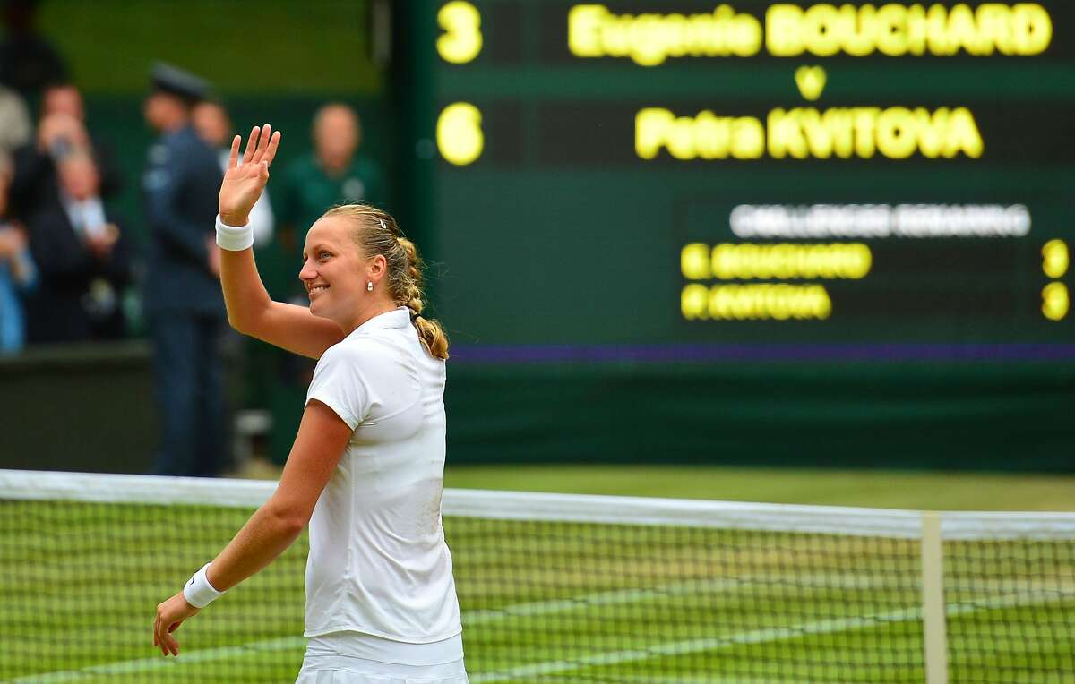 Czech Republic's Petra Kvitova waves as she celebrates winning her women's singles final match against Canada's Eugenie Bouchard on day twelve of the 2014 Wimbledon Championships at The All England Tennis Club in Wimbledon, southwest London, on July 5, 2014. Kvitova stormed to her second Wimbledon title in the shortest women's final at the All England Club since 1983 as the Czech sixth seed crushed Canada's Eugenie Bouchard 6-3, 6-0. AFP PHOTO / CARL COURT - RESTRICTED TO EDITORIAL USECARL COURT/AFP/Getty Images