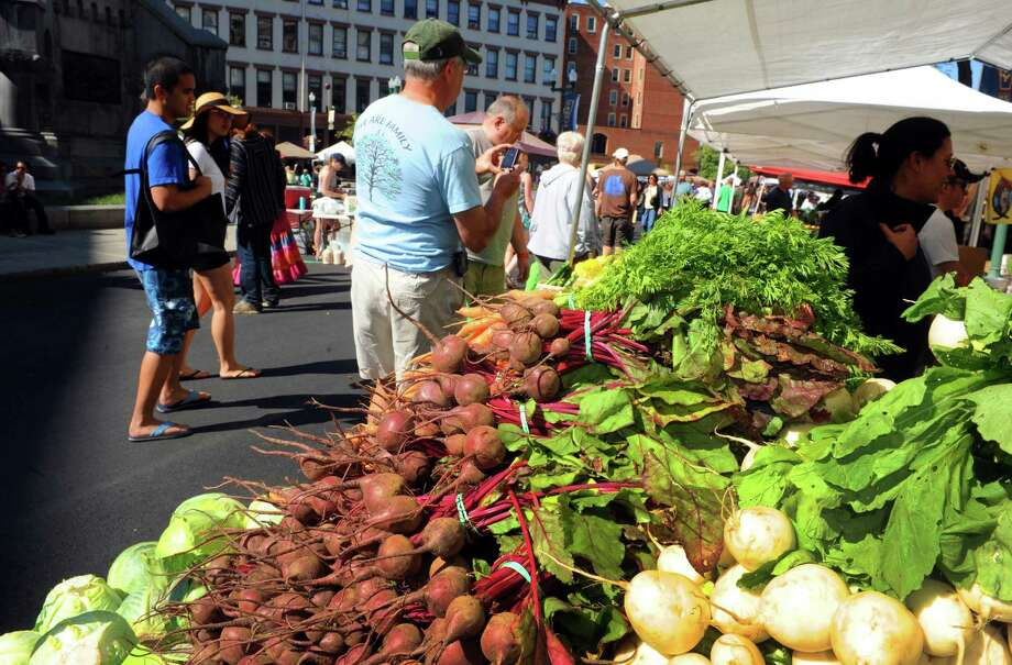 A busy market place with fresh produce for sale at the Little Seed Gardens booth during the Troy Farmers Market on Saturday July 5, 2014 in Troy, N.Y. (Michael P. Farrell/Times Union) Photo: Michael P. Farrell / 00027640A