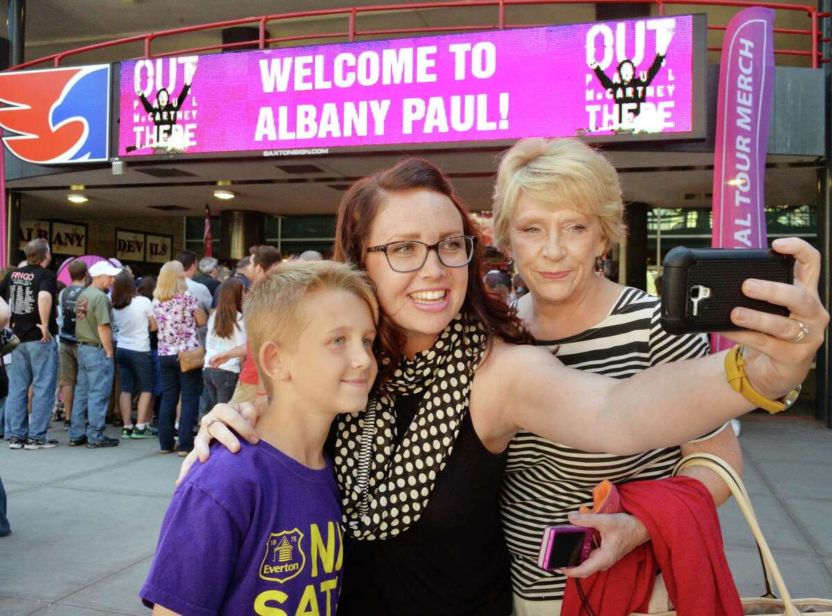 Three generations of Beatles fans, from left, 10-year-old Joshua Moon, his mom Kelly Moon and grandmother Joan Walton, all of Niagara Falls, Canada, take a selfie as they arrive at the Times Union Center for the Paul McCartney Out There tour concert Saturday July 5, 2014, in Albany, NY. Originally from Liverpool, Joan Walton had seen the Beatles at the Cavern Club and has remained a fan all these years. (John Carl D'Annibale / Times Union)