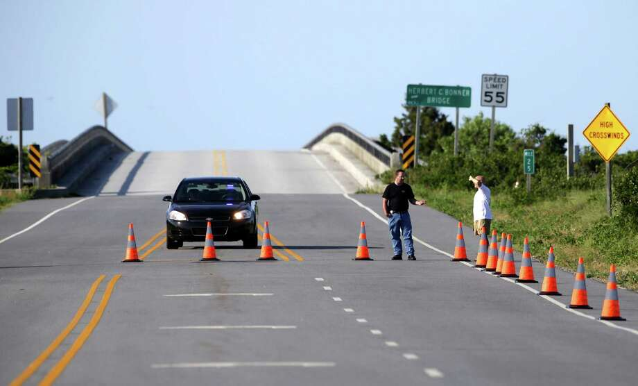A police checkpoint prevents traffic from crossing the Bonner Bridge on Highway 12 while safety inspections continue following Hurricane Arthur's impact on the Outer Banks near Nags Head, N.C., Saturday, July 5, 2014. Businesses on two of North Carolina's barrier islands hoped to salvage the rest of the holiday weekend after Arthur clipped the state without causing major damage before churning north toward Canada and losing strength early Saturday morning. (AP Photo/Gerry Broome) Photo: Gerry Broome, STF / AP