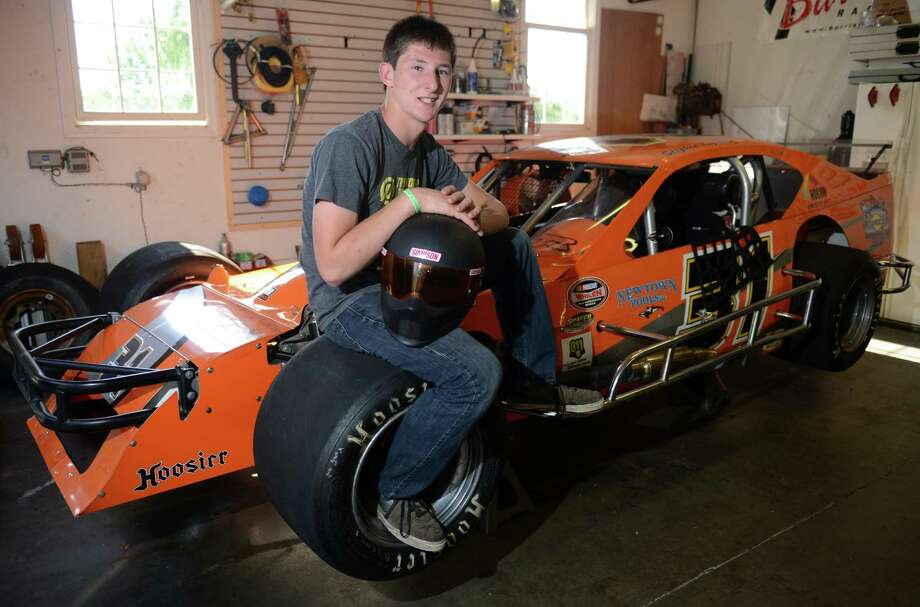 Steven Kopcik, 16, poses by his race car inside the garage of his Newtown, Conn. home on Saturday, July 5, 2014.  Kopcik began racing go-karts at age 12, then moved up to U.S. Legends race cars, and this year began running a modified stock car at Stafford Motor Speedway. Photo: Tyler Sizemore / The News-Times