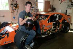 Steven Kopcik, 16, poses by his race car inside the garage of his Newtown, Conn. home on Saturday, July 5, 2014.  Kopcik began racing go-karts at age 12, then moved up to U.S. Legends race cars, and this year began running a modified stock car at Stafford Motor Speedway.