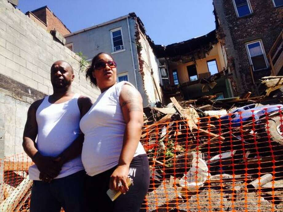 Rasheem and Jamie Robinson stand before the rubble of the brownstone at 162 Clinton St. in Albany that collapsed Friday next door to their home. (Cindy Schultz/Times Union)