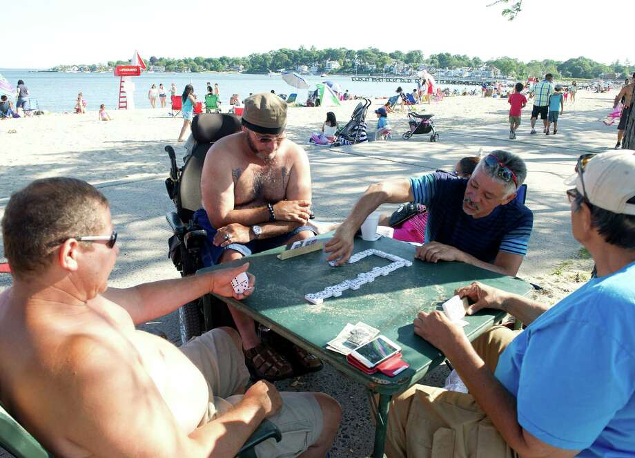 Clockwise from top, Edwin Sanchez, Joaquin Sanchez, Antonio Colon and Carlos Cabrera play dominoes while waiting for the fireworks at Cummings Beach on Saturday, July 5, 2014. Photo: Lindsay Perry / Stamford Advocate