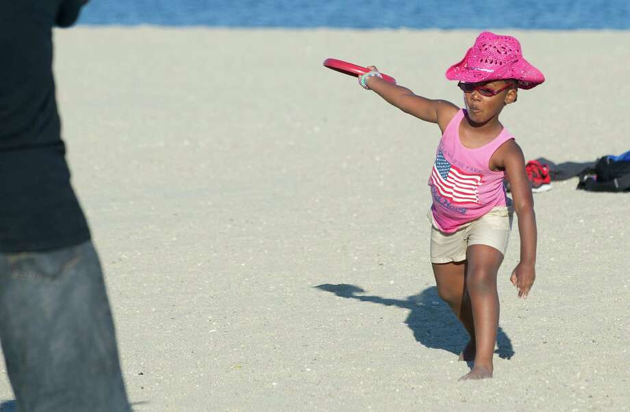 Nia Forbes, 4, learns how to throw a frisbee while waiting for the fireworks at Cummings Beach on Saturday, July 5, 2014. Photo: Lindsay Perry / Stamford Advocate