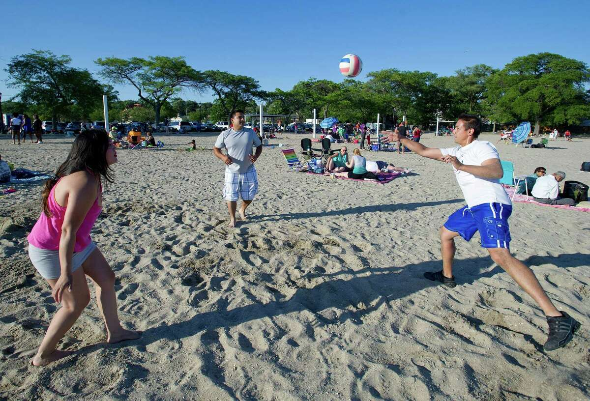 From left, Gloria Anchundia, Carlos Ribera and Ramon Hernandez play volleyball while waiting for the fireworks at Cummings Beach on Saturday, July 5, 2014.