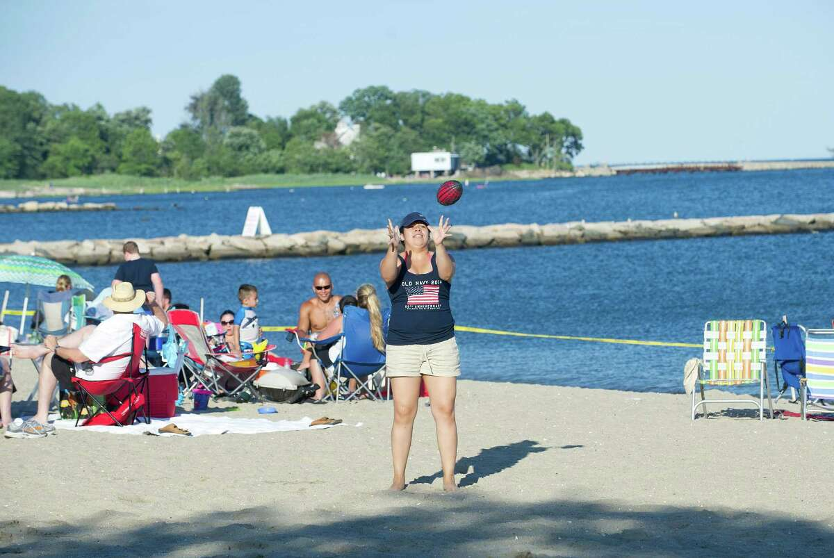 Beachgoers play football while waiting for the fireworks at Cummings Beach on Saturday, July 5, 2014.
