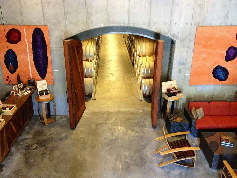 The tasting room lobby of Jericho Canyon Vineyard in Calistoga features red sofas, barrel-stave rocking chairs and a polished wood bar. Tastings are held in the 6,000-square-foot cave off the winery lobby. Photo: Jericho Canyon