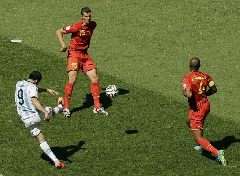 Gonzalo Higuain scores between Belgium's Daniel Van Buyten and Vincent Kompany. Photo: Thanassis Stavrakis, Associated Press