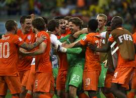 Netherlands players celebrate after the quarter-final football match between the Netherlands and Costa Rica at the Fonte Nova Arena in Salvador during the 2014 FIFA World Cup on July 5, 2014. AFP PHOTO / ODD ANDERSENODD ANDERSEN/AFP/Getty Images