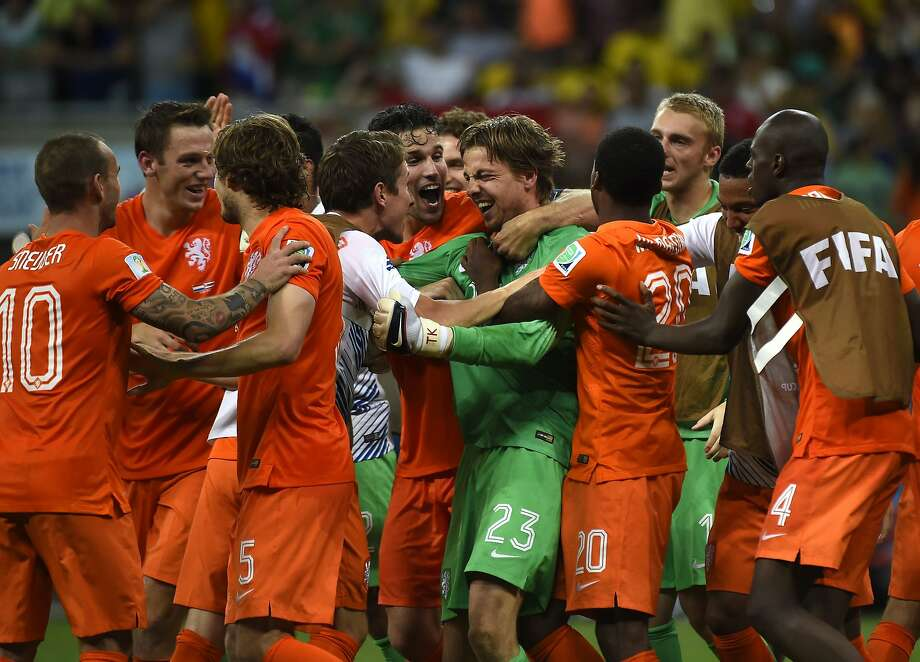 Netherlands players celebrate after the penalty-kick shootout against Costa Rica went their way. The Dutch, who lost in the final to Spain in 2010, are back in the semifinals. Photo: Odd Andersen, AFP/Getty Images