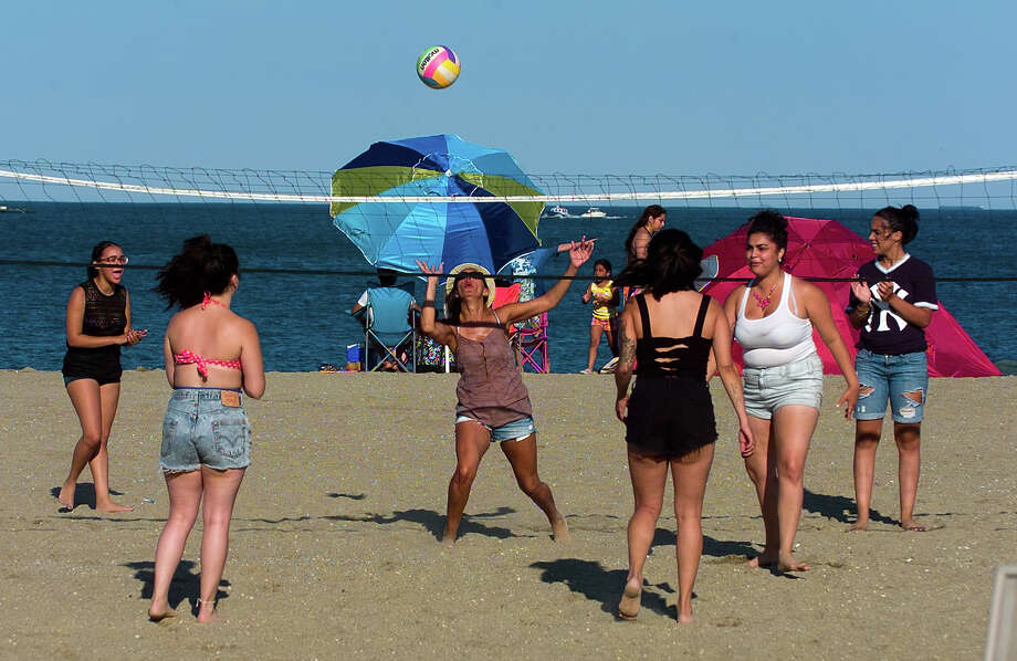 Millie Lopez, of Stratford, in center, reaches to return the ball as she plays volleyball with her cousins as they await fireworks at Short Beach Park in Stratford, Conn. on Saturday July 5, 2014. Photo: Christian Abraham / Connecticut Post