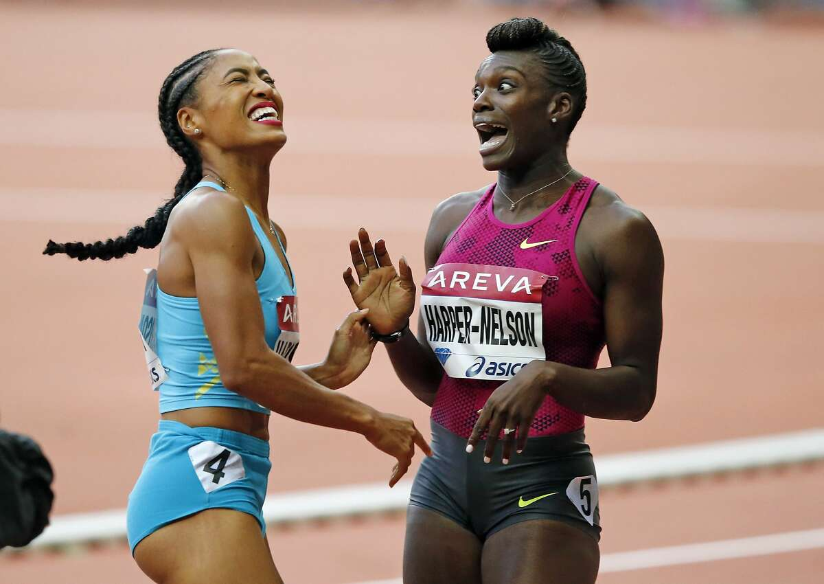Dawn Harper Nelson of the U.S. , right, reacts after winning the 100m Hurdles Women's race ahead of Queen Harrison of the U.S. during the Athletics Diamond League meeting at Stade de France stadium, in Saint Denis, north of Paris, France, Saturday, July 5, 2014. (AP Photo/Francois Mori)