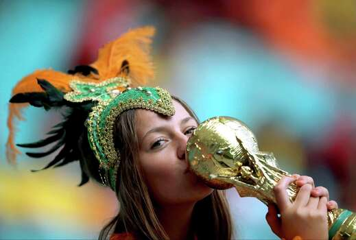 A fan of the Netherlands kisses a replica of the World Cup before the World Cup quarterfinal soccer match between the Netherlands and Costa Rica at the Arena Fonte Nova in Salvador, Brazil, Saturday, July 5, 2014. (AP Photo/Hassan Ammar) Photo: Hassan Ammar, Associated Press / AP