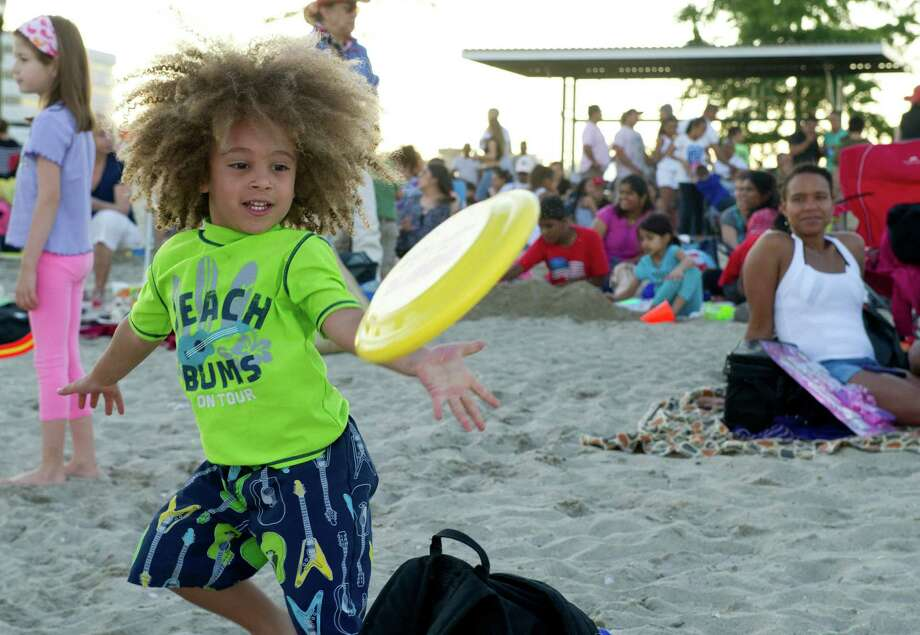 Michael Colon, 3, plays frisbee while waiting for the fireworks at Cummings Beach on Saturday, July 5, 2014. Photo: Lindsay Perry / Stamford Advocate