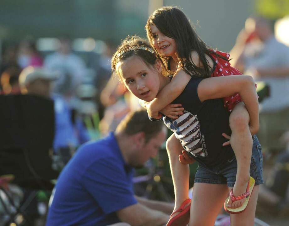 "Ava Vondle, 7, of Danbury, carries Cassidy Morehouse, 4, of Ridgefield, on her shoulders while listening to music by ""Fast Ricky"" at the Annual Fireworks Celebration at the Danbury Fair in Danbury, Conn. Saturday, July 5, 2014.  Originally scheduled for July 3, the fireworks celebration featured live music by ""Fast Ricky"" and ""The Zoo"" with kids inflatables and games, topped off by a fireworks show over the mall at 9:30. Photo: Tyler Sizemore / The News-Times"