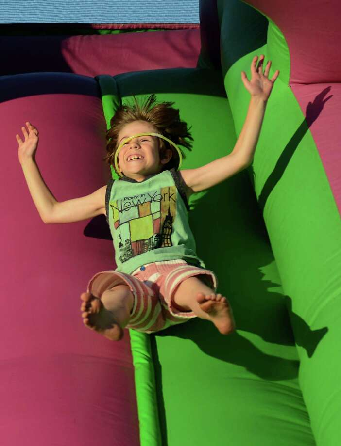"""Max Rand, 7, of Mount Kisco, N.Y., bounces down the kids slide at the Annual Fireworks Celebration at the Danbury Fair in Danbury, Conn. Saturday, July 5, 2014.  Originally scheduled for July 3, the fireworks celebration featured live music by """"Fast Ricky"""" and """"The Zoo"""" with kids inflatables and games, topped off by a fireworks show over the mall at 9:30. Photo: Tyler Sizemore / The News-Times"""