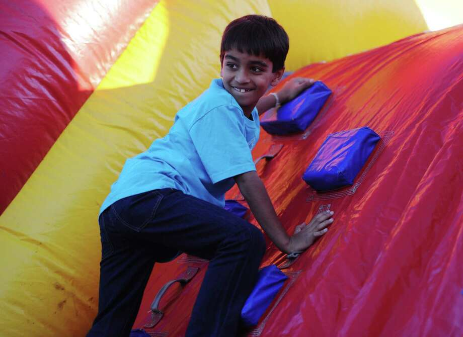 "Bhavin Shah, 8, of Atlanta, climbs an inflatable during the Annual Fireworks Celebration at the Danbury Fair in Danbury, Conn. Saturday, July 5, 2014.  Originally scheduled for July 3, the fireworks celebration featured live music by ""Fast Ricky"" and ""The Zoo"" with kids inflatables and games, topped off by a fireworks show over the mall at 9:30. Photo: Tyler Sizemore / The News-Times"