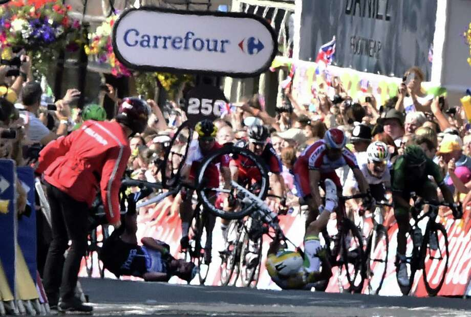 Britain's Mark Cavendish (left) and Australia's Simon Gerrans collide and fall near the finish line of the first stage of the Tour de France in Harrogate, England. Cavendish separated his right shoulder, and his team will decide if he rides in Stage 2 today. Photo: Lionel Bonaventure / Getty Images / AFP