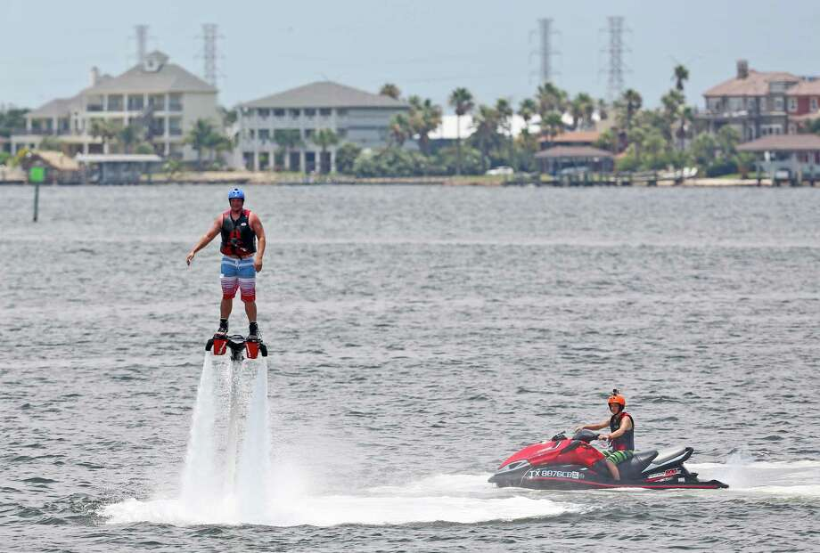 Clinton Phifer from Ocean Springs, Miss. Flyboard while Hunter Verlander controls the jet ski in the Ouffats Bayou in Galveston. Photo: Thomas B. Shea, For The Chronicle / © 2014 Thomas B. Shea