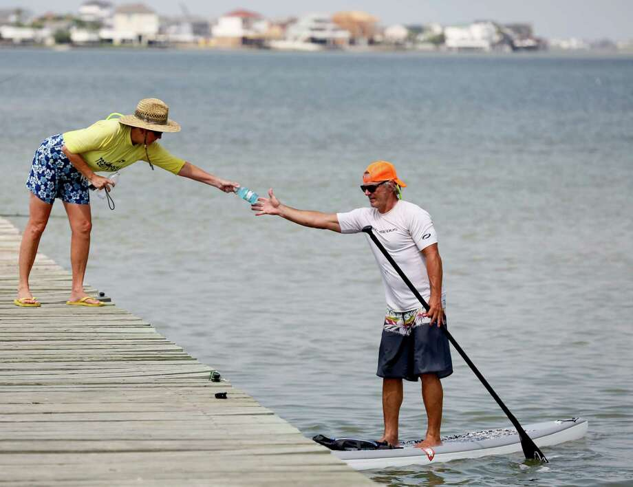 Angela hands her husband Jimmy Mooney, from Houston, a drink while he take a break from learning how to paddle board in the Galveston Bay. Photo: Thomas B. Shea, For The Chronicle / © 2014 Thomas B. Shea