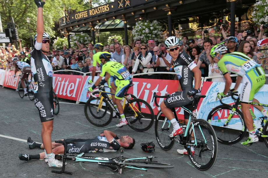 Britain's Mark Cavendish, lying on the pavement, separated his right shoulder in Saturday's spill, putting his status for today's Stage 2 in question. Photo: FRED MONS, Staff / AFP