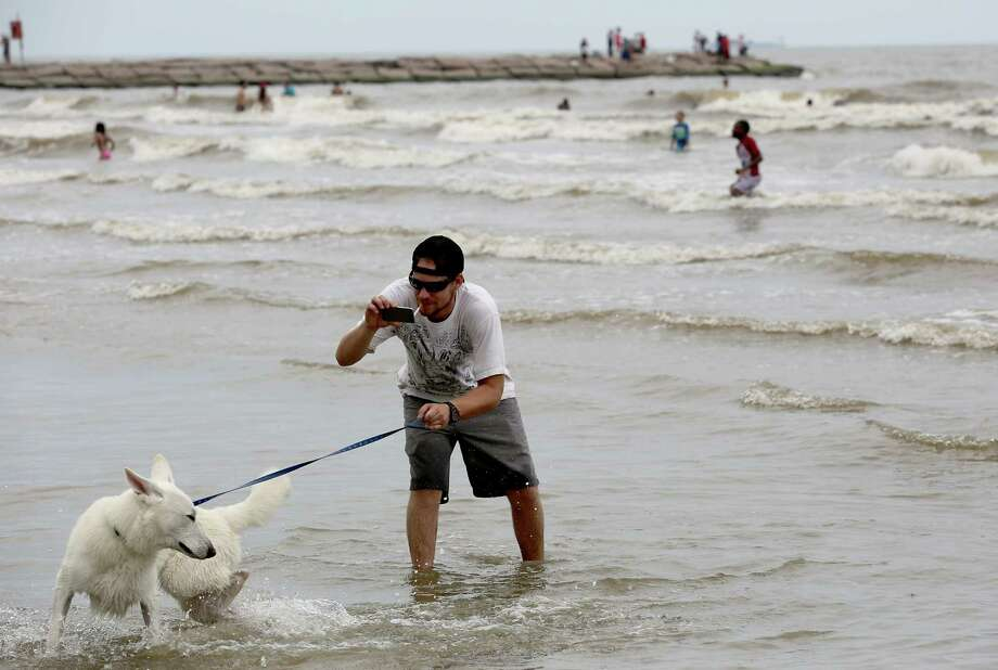 Joshua Lambert photographs his white German Shepard, Tucker  in the water at Galveston Beach. Photo: Thomas B. Shea, For The Chronicle / © 2014 Thomas B. Shea