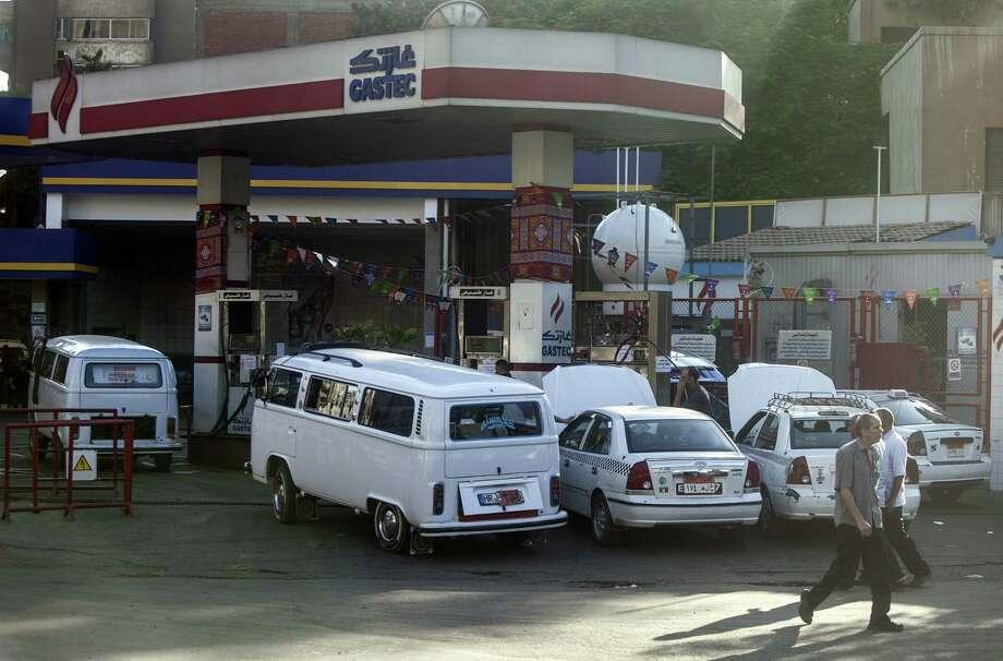 """Egyptians in their white vehicles gather at a gasoline station, where prices rose by as much as 80 percent. """"Where am I supposed to get money from?"""" says one taxi driver. Photo: Mahmoud Khaled / AFP / Getty Images / AFP"""