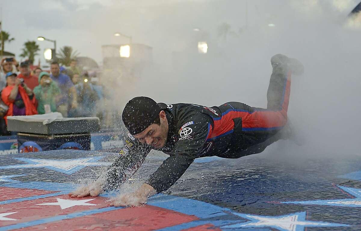 Ryan Truex dives on the rain-slick runway during introductions before the NASCAR Sprint Cup series auto race at Daytona International Speedway in Daytona Beach, Fla., Saturday, July 5, 2014. The race was later postponed until Sunday morning. (AP Photo/Phelan M. Ebenhack)