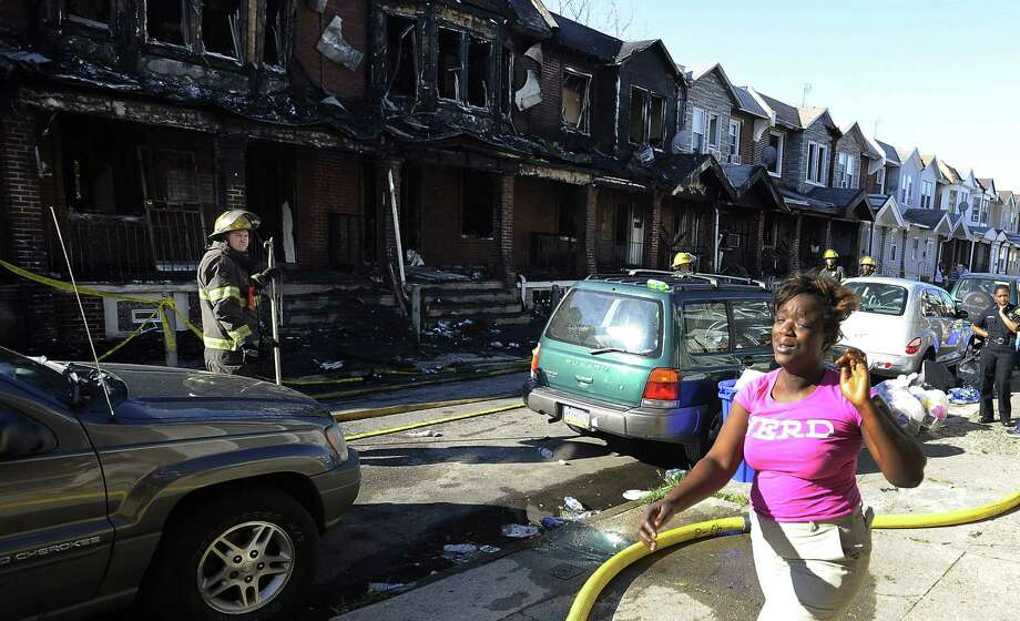 A woman cries as she walks past Philadelphia firefighters working on burned row houses. The fast-moving fire, perhaps spreading from a porch couch, engulfed at least 10 houses. Photo: Michael Perez / Associated Press / FR168006 AP