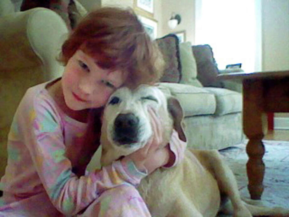 Catherine Hubbard hugs family pet Sammy at their home in Newtown, Conn. Her dream of helping animals is close to becoming a reality. Photo: Jenny Hubbard, HONS / Jenny Hubbard