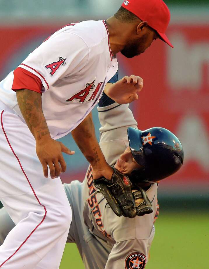 Among the things rookie George Springer, right, is learning is that it can be tough on the basepaths as he takes a tag on the chin from the Angels' Howie Kendrick. Photo: Mark J. Terrill, STF / AP