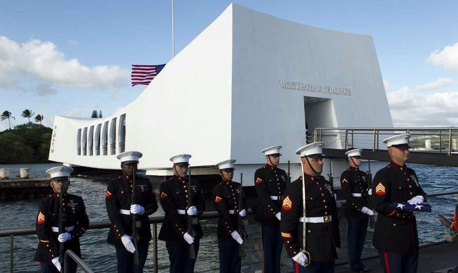 Marines stand at attention as a family arrives to have the ashes of a relative who was aboard the USS Arizona when the Japanese attacked interred on the ship. Photo: Associated Press / File Photo / AP2011