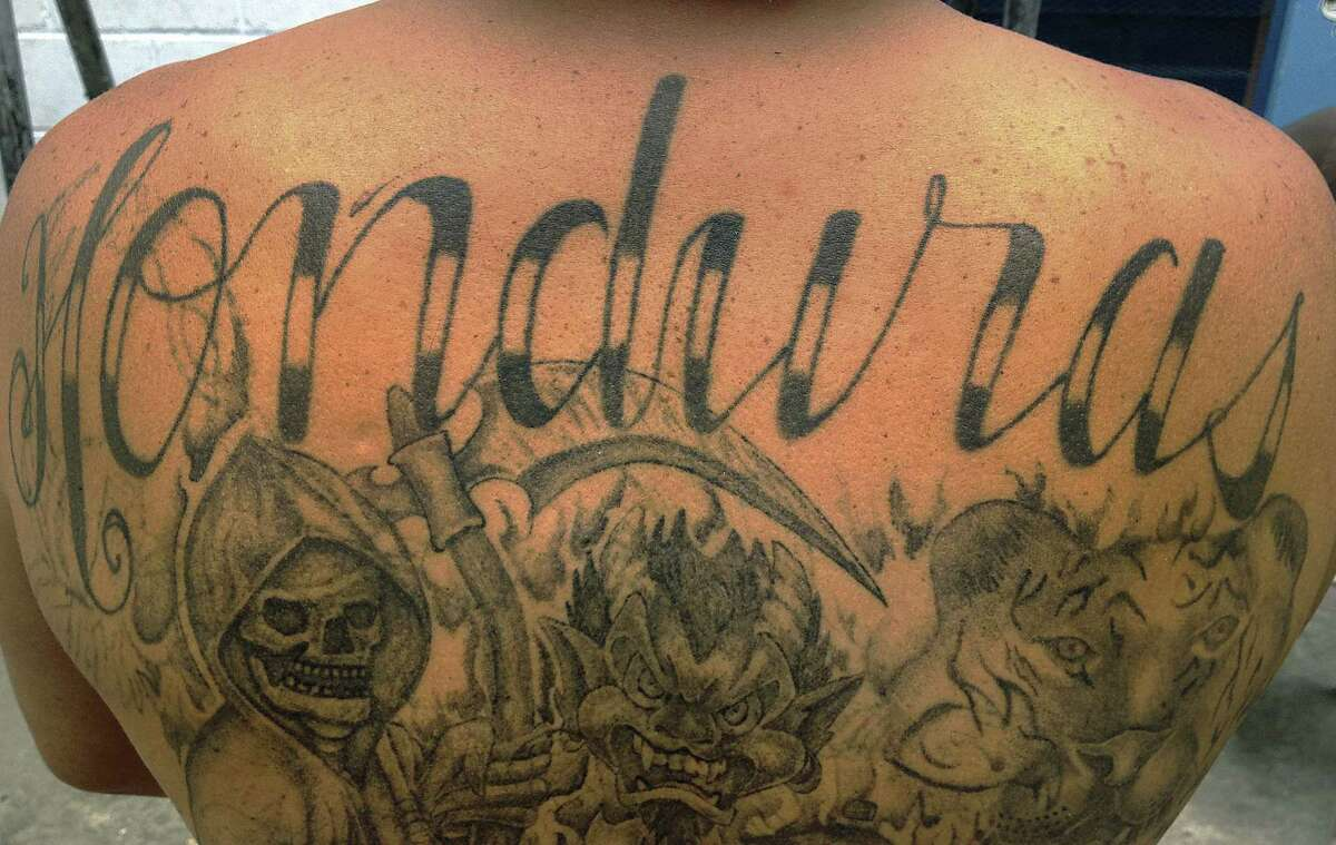 An imprisoned former gang member displays the marks of his former life.