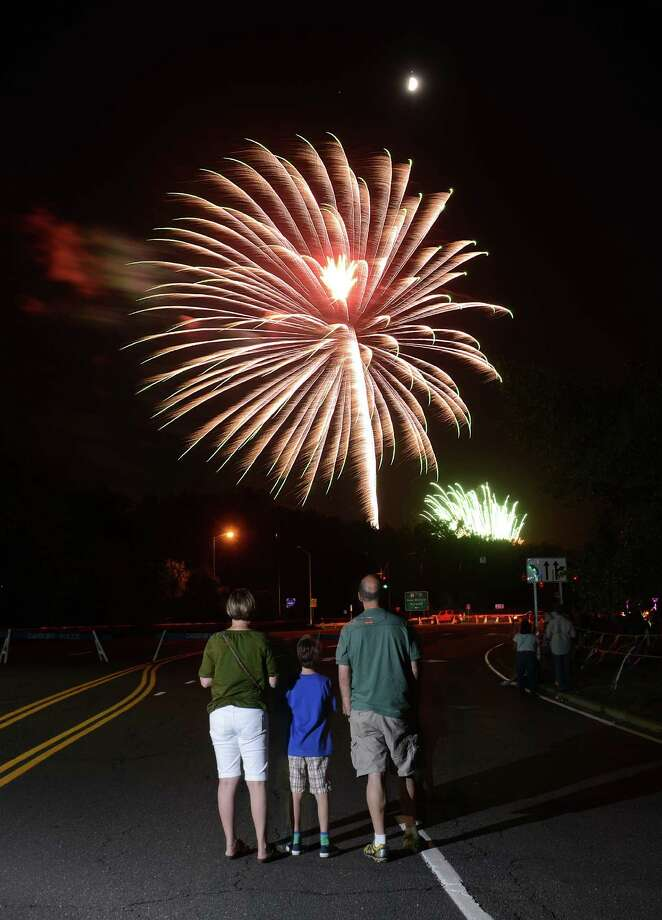 "George Caratzas, 8, stand between his parents Natasha and Peter Alexander, of South Salem, N.Y., to watch fireworks at the Annual Fireworks Celebration at the Danbury Fair in Danbury, Conn. Saturday, July 5, 2014.  Originally scheduled for July 3, the fireworks celebration featured live music by ""Fast Ricky"" and ""The Zoo"" with kids inflatables and games, topped off by a fireworks show over the mall at 9:30. Photo: Tyler Sizemore / The News-Times"