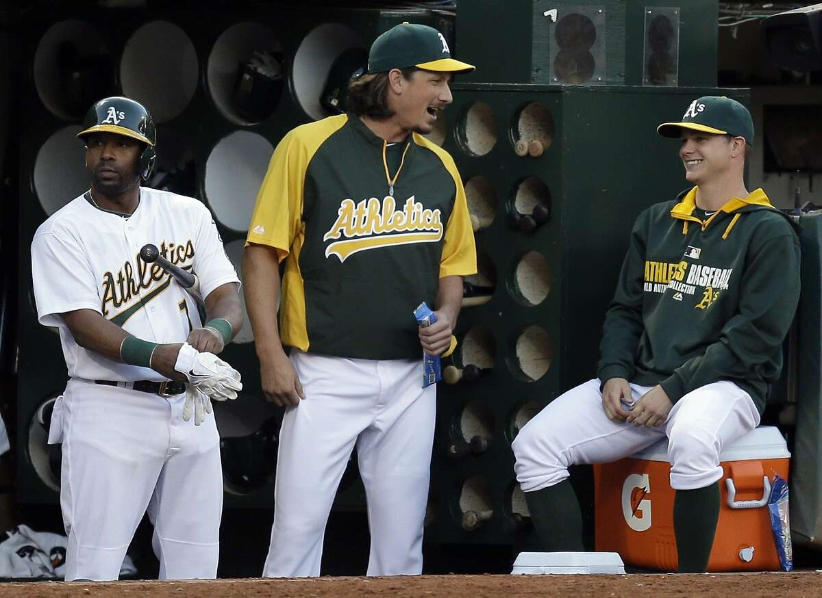 Oakland Athletics' Jeff Samardzija, center, speaks with pitcher Sonny Gray, right, in the fourth inning of a baseball game against the Toronto Blue Jays on Saturday, July 5, 2014, in Oakland, Calif. Samardzija was acquired in a trade from the Chicago Cubs. At left is A's Alberto Callaspo. (AP Photo/Ben Margot)