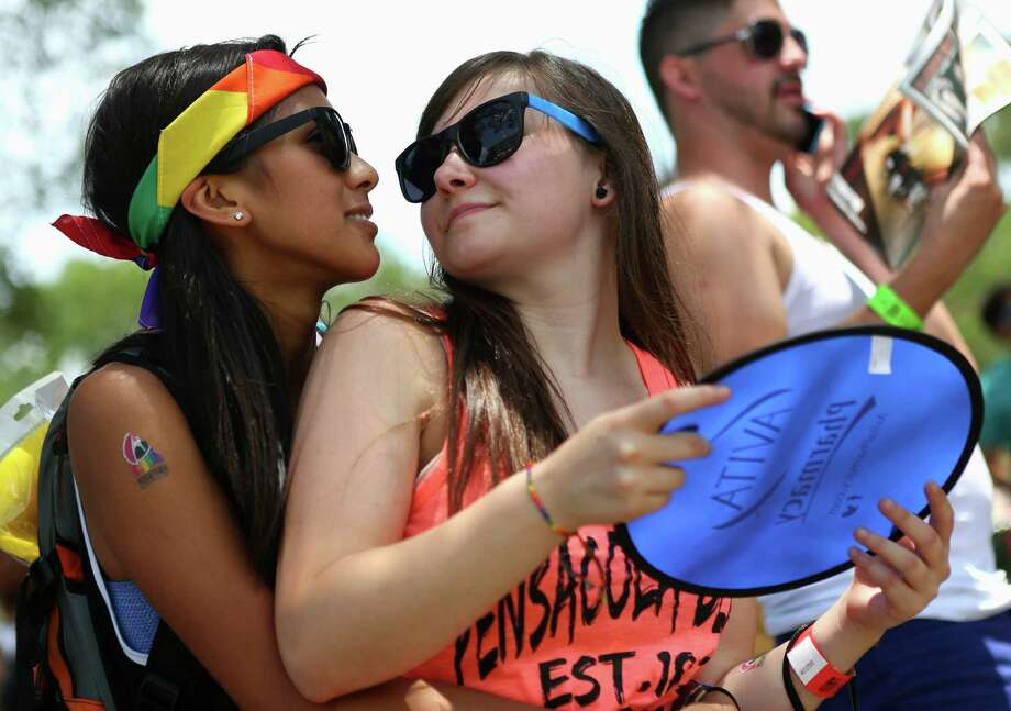 Cielo Agabon, 20, left, hugs her girlfriend, Desirae Logray, 17, during Pride San Antonio's Pride Bigger Than Texas festival on Saturday, July 5, 2014, at Crockett Park in San Antonio. Agabon said this is her third year attending the annual festival, while Logray said it was her first time at the event. Photo: Timothy Tai, Timothy Tai, Express-News / © 2014 San Antonio Express-News