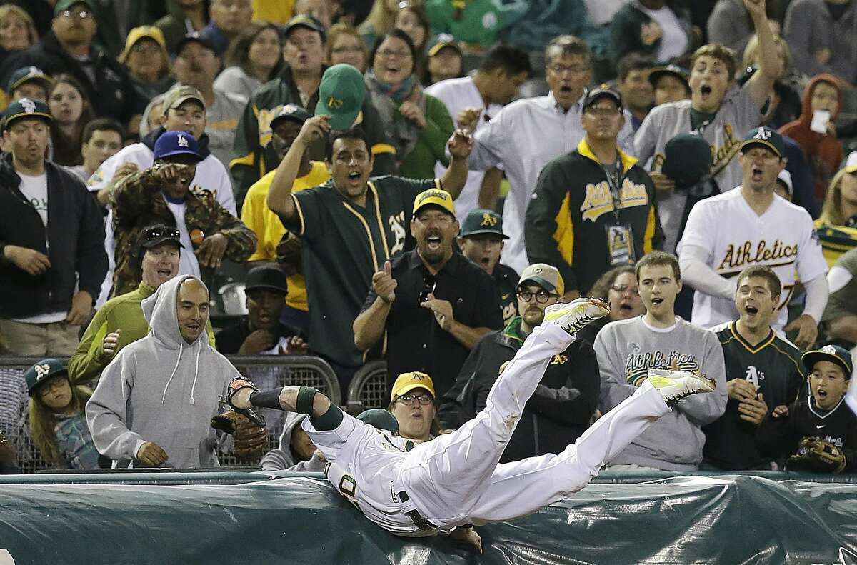 Oakland Athletics' Josh Donaldson catches a foul ball hit by Toronto Blue Jays' Munenori Kawasaki in the eighth inning of a baseball game Saturday, July 5, 2014, in Oakland, Calif. (AP Photo/Ben Margot)