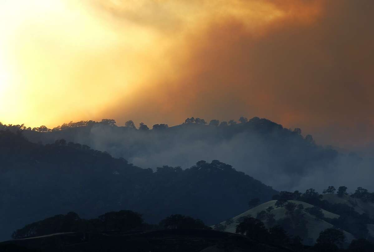 Smoke rises as the sun sets on the Monticello Fire near Lake Berryessa where the Solano, Napa and Yolo county lines converge July 5, 2014 near Winters, Calif.