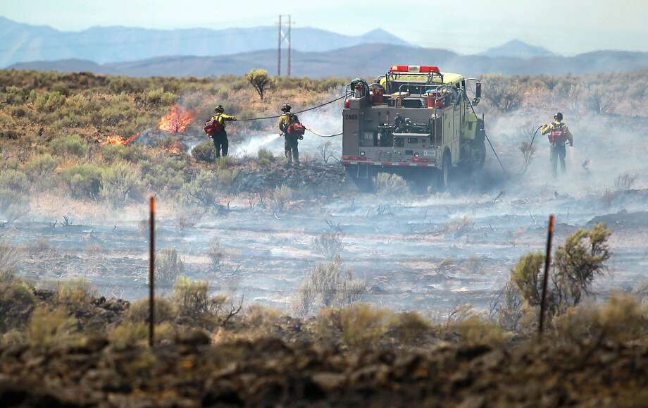 Bureau of Land Management firefighters work to extinguish a brush fire along U.S. Highway 26 at mile marker 188 near Dietrich, Idaho on Saturday, July 5, 2014. The fire that started Friday afternoon reached about 130 acres Saturday morning.  Photo: Drew Nash, Associated Press