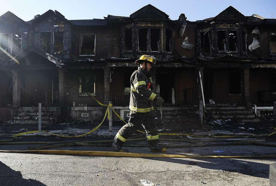 A Philadelphia firefighter walks past burned adjoining homes on Saturday, July 5, 2014, in Philadelphia. Authorities say the fast-moving fire early Saturday has killed four children. Fire department officials say there is no immediate word on how many others were injured in the blaze that destroyed eight homes in the row and engulfed a total of 10 houses. (AP Photo/Michael Perez) Photo: Michael Perez, Associated Press