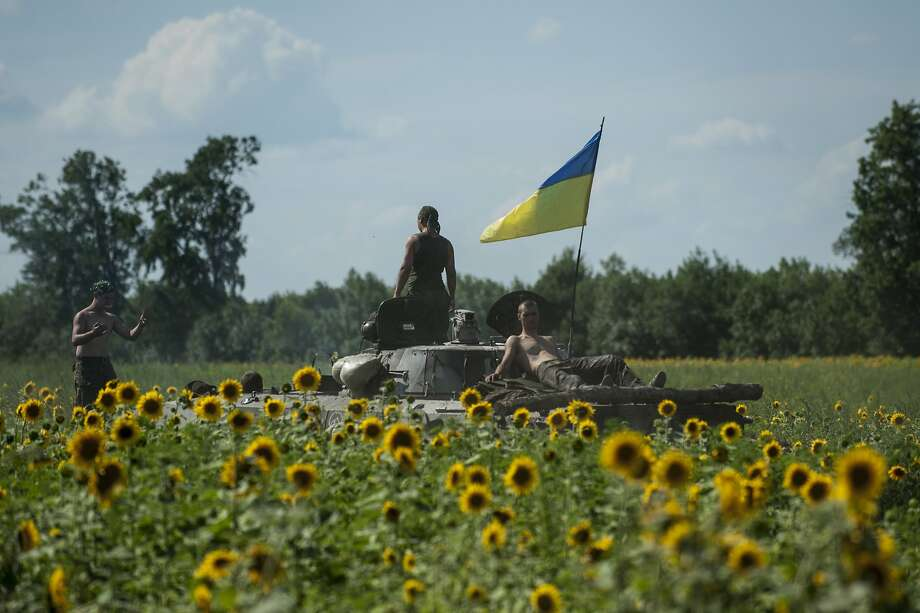 Ukrainian troops ride on an APC with a Ukrainian flag, in a field with sunflowers in Kryva Luka, eastern Ukraine, Saturday, July 5, 2014. Ukraine's forces claimed a significant success against pro-Russian insurgents on Saturday, chasing them from one of their strongholds in the embattled east of the country. Rebels fleeing from the city of Slovyansk vowed to regroup elsewhere and fight on.  (AP Photo/Evgeniy Maloletka) Photo: Evgeniy Maloletka, Associated Press