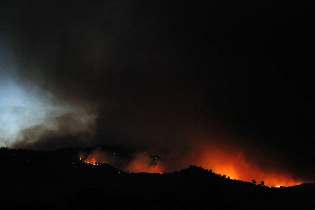 Fire licks the mountainside as fire fighters begin to work into the night to contain the Monticello Fire near Lake Berryessa where the Solano, Napa and Yolo county lines converge July 5, 2014 near Winters, Calif.